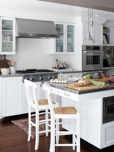 Stainless steel countertops bring a hint of industrial gleam to the kitchen of this Kansas home. Furnished with Pottery Barn stools painted white to match the custom cabinets, the island provides a place to sit while prepping food.