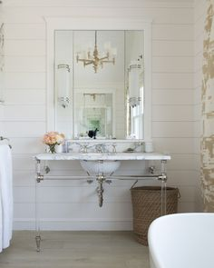Ethereal bathroom features a rope chandelier which is suspended over an oval freestanding tub placed in front of windows dressed in taupe toile curtains, Quadrille Paradise Background Taupe on Tint Fabric, illuminated by a rope chandelier. An extra-wide nickel and brass washstand with marble top stands under a white framed vanity mirror fitted with sconces lining white shiplap walls atop plank floors.