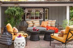 On the patio of a Menlo Park, California, house designed by Matthew Leverone, the slate-blue tones of Restoration Hardware's Carmel daybed, Pottery Barn's Frog Rain drum side tables, and Brown Jordan's Venetian chairs echo the house's siding. Pillows in Schumacher's Sunglass Print and Duralee's Pavilion.