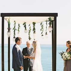 """""""Other than my bouquet of flowers, I didn't want any other petals so I had the aisle lined in fresh potted herbs.   The chairs and arbor that we were married under were a dark mahogany wood and strung with antique pendants.  Guests were tray passed champagne while they took in the sweeping views!"""" Julie says. Wedding Ceremony Backdrop, Ceremony Arch, Wedding Arches, Aisle Style, Hanging Lanterns, Event Decor, Altar, Potted Herbs, Dark Mahogany"""