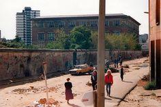 Nach der Wende. Ein typisches Bild. Die zerhackte Mauer, ein demolierter Westwagen und der Müll liegt auf der Straße. Im Jahre 1990 wirkte Berlin an manchen Stellen orientierungslos! Aus dem Bus fotografiert, daher mit Laterne im Vordergrund. Scan eines Fotos aus dem Jahre 1990