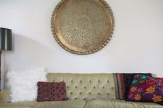 A brass table top found at an estate sale is used as wall decor in the living room. Throw pillows are faux fur and oversized velvet pillows from ikea, embroidered pillows are a gift from her mom's trip to Mexico. Kilim pillows were estate sale finds.