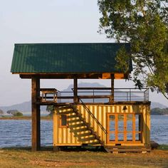 This is a lakeside container turned cabin in Sri Lanka. It was built by soliders in an army training camp using the container and timber from weapon boxes that the soldiers found around the area.