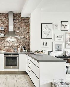 Love this bright open space. Exposed brick in the kitchen and then transitioning into a beautiful gallery wall!