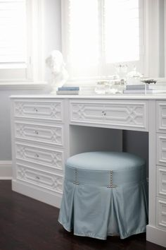 Dark hardwood floors contrast an eye catching white trellis make up vanity with round glass pulls topped with a white jewelry bust and sat in front of bay windows covered in white plantation shutters framed by light blue walls that coordinate with a round blue vanity stool completed with a pleated skirt.