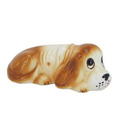 Pre-owned vintage used ceramic decorative collectible dog figurine with gloss glaze finish.  I believe this is a beagle or similar breed.  The brown and white puppy dog is laying down with its head between its front paws and a sad expression on its face.  The figurine would be a great addition to an existing dog collection or a wonderful decorative accent home decor piece.  #EverythingsCollectible #CollectItAll #Dog #Figurine