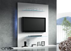PANELES TV El panel TV es un nuevo mueble de pared para tu hogar que ayuda a resolver el problema de instalación de la pantalla TV en cualquier estancia. No necesitas grandes espacios para poder disfrutar de la TV junto con los demás aparatos como reproductores, consolas, colección de DVD's. Todo en un solo mueble que ahorra espacio al estar dispuesto en la pared que elijas. De venta en Mobles Cambrils. Buscanos. Deco Tv, Tv Rack, Tv Panel, Entertainment Wall, Wall Mounted Tv, Tv Cabinets, Home Projects, Living Room Decor, Living Rooms