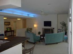 Contemporary living room neon lights terrazo flooring round couch Frostwood, Houston TX