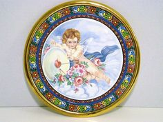 Cearco Decorative Plate hand painted Spain 24 kt gold trim. Cearco decor from Seville, Spain. The decorative plate with Cupid and his arrow through the heart is surrounded by clouds and resting on a beautiful bouquet of flowers. Intricate detail of this artisan hand-painted plate with colorful floral designed border and trimmed with 24k gold