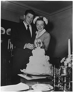 Newlyweds Ronald Reagan and Nancy Reagan cutting their wedding cake, 03/04/1952
