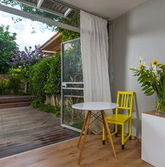 A small round table and a yellow chair in Liat Hadas' office, next to the garden. By Liat Hadas, Architecture & Design. #Design #Architecture #Table #lifestyle #Colors #Mediterranean #View  #Styling #textile #Library #Wood  #furniture  #Walldecor #Wallcolor  #storage #storagedesign #Covertstorage #storage  #Officedesign #OFFICESTORAGE
