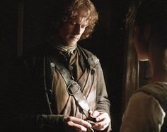 Claire gives Jamie the wooden snake (Sawny), made for him by Willie.