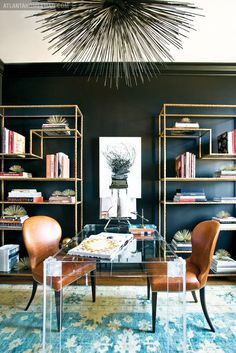 Dark library with gold bookcases, lucite table, and leather chairs.