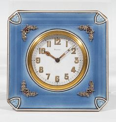 A silver and guilloché enamel desk clock. Square, enamelled in opalescent blue over guilloché ground, centring a white enamel dial, set with laurel branches set with rose-cut diamonds.