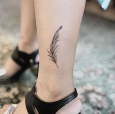 Detailed feather tattoo by Nando