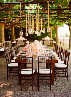 long tables under arbors - love the faux chandeliers with votives hanging from ribbon