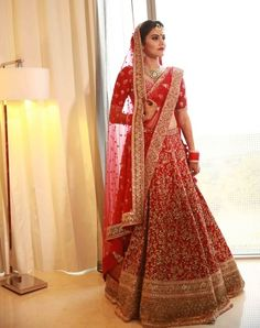 red bridal outfit with intricate golden embroidery  #Trending, #TrendingBridalWear, #BridalWearInspirations, #LehengaInspirations, #TrendingLehengas, #BridalLehengas, #BridalWear, #RedLehengas, #PastelLehengas, #Sabyasachi