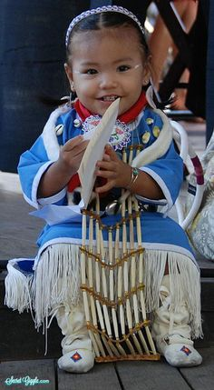A Native American girl, around 3 years old, smiling in her beautiful traditional outfit.