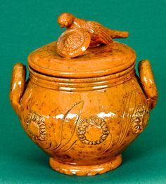 $ 2990  Rare Glazed Redware Lidded Sugar Bowl with Bird Finial, attributed to James C. Mackely, Mechanicstown (now Thurmont), MD, circa 1875, bulbous sugar bowl with rounded foot, tooled collar, and open loop handles. Decorated on both sides with applied flower blossoms connected by an incised stem with leaves. Lid decorated with a large hand-modeled and incised bird with head above an unusually large, heavily-incised flower blossom. Surface decorated with daubs of manganese and covered in a…
