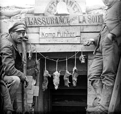 Two German officers pose in front of their dug-out, decorated with strung-up rats. Catching rats was a popular hobby among the troops; the stolen French business signs seems to be a matter of taste.