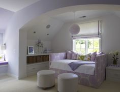 Adorable lilac girl's bedroom with lilac walls paint color, beadboard ceiling, purple daybed, white built-ins with woven baskets, white linen roman shade with purple ribbon trim and round white leather ottomans.