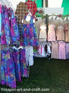 Handmade children's clothing displayed on gridwalls.  Note the vivid colors at the front of the booth. More booth photos at http://www.craftprofessional.com/clothing-displays.html