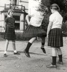 Onbekend   Drie meisjes in geruite Schotse rokjes spelen de elastiektwist. Op de foto zweeft één van hen boven het elastiek dat door de andere twee wordt opgehouden. Nederland, datum onbekend.