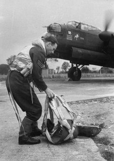 "The last member of the crew of a Avro Lancaster of No. 300 Polish Bomber Squadron getting ready his parachutes before boarding the aircraft for a sortie over Germany. Note the aircraft has its engines running. Photograph taken at RAF Faldingworth, summer 1944. The Lancaster is LL804, BH-F, ""Lady in the Champagne Glass"", commanded by Wing Commander Teofil Pożyczka, the CO of the squadron."
