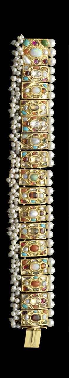 A gem-set enamelled gold Navratna Bracelet,nNorthern India, ca 1850-1900+. 15 rectangular and one square gold plaques set with a variety of semi-precious stones including coral, opal, turquoise and garnet, the central stone within an oval setting with four surrounding stones within a diamond shape and a further four stones to each corner, the reverse with enamelled birds on a floral ground, with small cultured pearls strung in groups above and a single line of larger cultured pearls below,