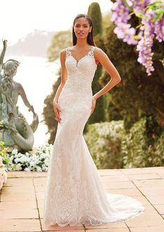 25267 - Meena - This V-neck fit and flare gown with sequined lace features a keyhole back. The chapel length train completes this beautiful look.  Try this beauty on at Aurora Bridal in Melbourne, FL 321-254-3880
