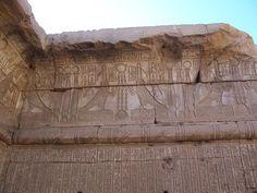 """Bas-reliefs présentant de nombreux hiéroglyphes dont le Bâ, répété plusieurs fois en grand format dans la frise supérieure. Le Bâ est représenté par un oiseau à tête humaine. C'est une composante immatérielle des dieux et des hommes. Ce concept est le plus souvent traduit par le mot """"âme"""" ou par l'expression """"âme-Ba"""". C'est la représentation de l'énergie de déplacement, de dialogue et de transformation. Il se distingue du Ka qui s'apparente au corps - Temple de la déesse Hathor à Dendérah."""