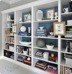 Blue background, books stacked, bowls of etc decor, framed art hanging on bookshelf,
