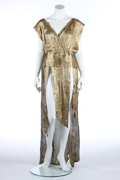 A beaded cloth of gold over-dress, early 1920s, with criss-cross bodice. wide sash belt, three short pointed floating panels to the front and a long tabard-like train to the back, fastening by prestud to inner waistband.