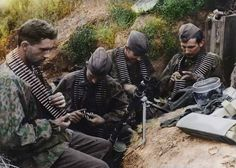 Colorized photo of Waffen SS soldiers linking ammo for an MG34 during the siege of Leningrad.