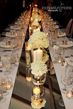 Mirrored table runner with silver mercury vase filled with white flowers and pretty candles