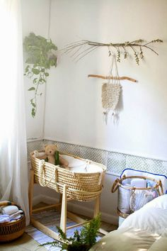 Neutral romantic nursery with handcrafted wall hangings and green plants by Latonya Yvette