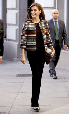 Queen Letizia, who kept her jewellery simple, stood tall in classic black court shoes and layered the jacket over a fine knit burgundy sweater