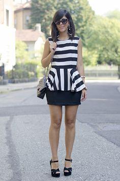 Un vestito peplum a righe bianche e nere ed una borsa Chanel