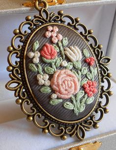 Hand embroidered peach pink and ivory flowers on a gray fabric with color cotton embroidery thread and put into vintage bronze style cameo base.