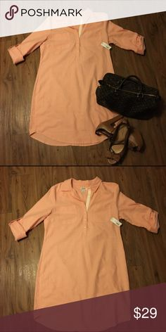 """Jean shirt dress """"NWT"""" This peachy colored shirt dress is an amazing spring/summer piece. It has rolled up sleeves as well as v neck trimmed with an white strip cotton piece. Pairs well with booties and crossbody bags 100% cotton """"NEVER BEEN WORN"""" Old Navy Dresses High Low"""