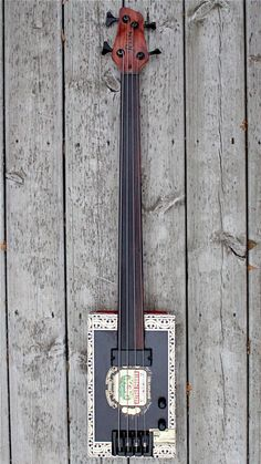 32-inch scale fretless cigar box bass guitar with maple neck with adjustable truss rod and rosewood fingerboard, side dot markers, soapbar pickup and vol & tone controls.