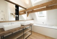 Inondato di luce naturale e protetto dalla travi a vista, il bagno padronale di questo casolare ristrutturato in Baviera è dotato di vasca e doppio lavabo in ceramica firmato Villeroy & Boch. Foto di: Benjamin A. Monn