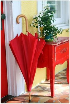 Red cabinet and red umbrella...great entry way to the home