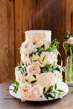 A three-tiered white buttercream wedding cake with flowers | Brides.com