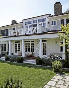 Cape Cod beautiful gray shingled home with simple square pillars, lanterns and Chippendale railing