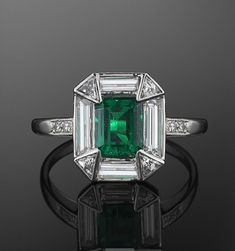 Platinum Emerald and Diamond Ring, c. 1920s.  A square emerald weighing approximately 0.75 carats is set in a halo of baguette and triangular diamonds in a platinum mounting.