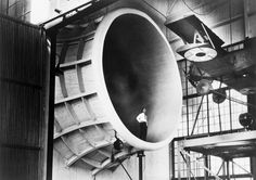 Man standing in giant wind tunnel with airplane suspended at upper right