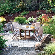 Rectangular chunks of tumbled Connecticut bluestone, set on a bed of decomposed granite and sand, form a 12-foot-diameter dining patio in a wooded Berkeley backyard.