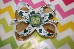 """Get your little girl ready for St. Patrick's Day with this festive hair bow. This hair bow is handmade our of gold ribbon and white and emerald shamrock ribbon. The hair bow is adorned with a bottle cap that says """"Lucky Me"""". It is secured to a ribbon lined alligator clip. Hair bow is heat sealed to prevent fraying of ribbon. Hair bow measures approximately 4 1/2""""."""