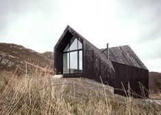 RAW Architecture Workshop have designed this angular black house at Camusdarach Sands with huge windows for taking in the views over the Scottish landscape. The shapes of these expansive gable windows are a play on… Architecture Résidentielle, Amazing Architecture, Workshop Architecture, Gable Window, Window Wall, Sand House, Highland Homes, Timber House, Black House